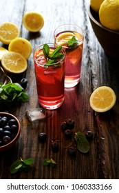 Cold honey blueberry lemonade in a glass. Dark wooden table