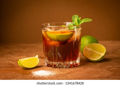Cold iced tea in a glass on a dark brown background. Close-up. Selective focus.