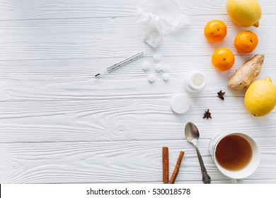 Cold illness, folk medicine and pills on a white wooden background. Ginger, lemon, cinnamon, badyan, tangerines and tea. The temperature on a thermometer.