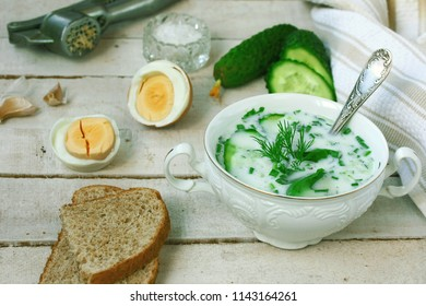 cold kefir soup with cucumber, herbs, boiled egg and garlic in white bowl on wooden table