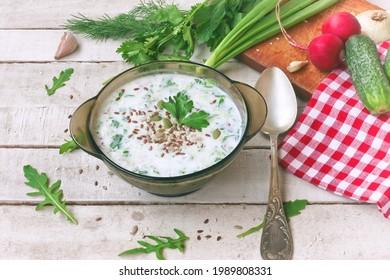 sopa de fir fría en tazón de vidrio con hierbas picantes, pepino, rábano sobre mesa blanca de madera, comida vegetariana, cerrar