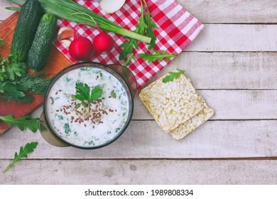 sopa de fir fría en tazón de vidrio con hierbas picantes, pepino, rábano sobre una mesa blanca de madera, comida vegetariana