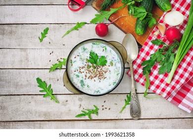 sopa de fir fría en tazón de vidrio con hierbas picantes, pepino, rábano sobre mesa blanca de madera, comida vegetariana