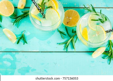 Cold lemonade or alcohol vodka cocktail with lemon and rosemary, on light blue table, copy space top view