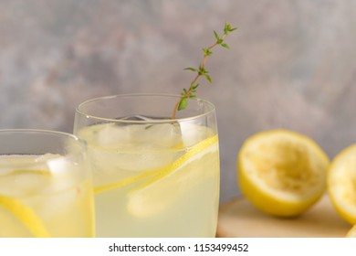 Cold lemonade or alcoholic cocktail with lemon, rosemary and ice in glass glasses on a light background.