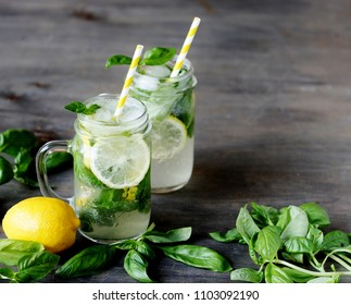 Cold lemonade with basil and lemon on a dark background. Soft focus. Place for text. Copy Space