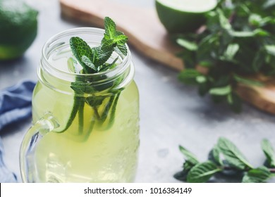 Cold lemonade mojito in a glass jar with lime and mint.