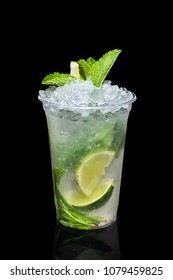 Cold lime and mint cocktail with a sparkling wine with ice in take away glass isolated on black