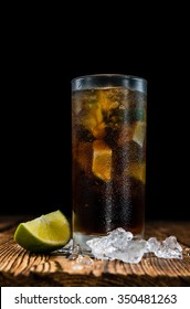 Cold Longdrink (Cuba Libre) with brown rum and fresh lime on rustic wooden background