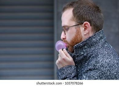 Cold Man with Beard Blowing a Bubble with a Bubblegum