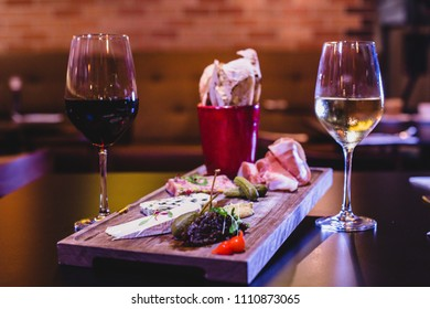 Cold meat and cheese platter with wine