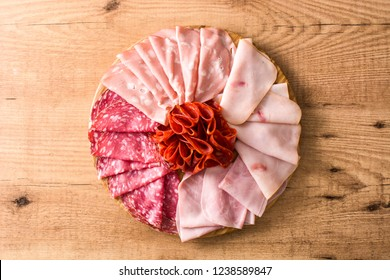 Cold meat on cutting board on wooden table. Ham, salami, sausage mortadella and turkey. Flat lay top-down