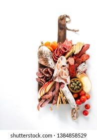 Cold meat plate, charcuterie on white background with copy space. Traditional Spanish tapas selection - chorizo, salchichon, jamon serrano, lomo, salami. Top view.