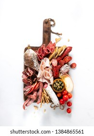 Cold meat plate, charcuterie on white background with copy space. Traditional Spanish tapas selection - chorizo, salchichon, jamon serrano, lomo, salami.