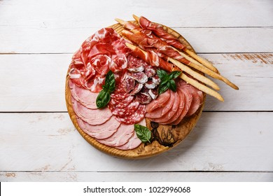 Cold meat plate Italian snacks food with ham, prosciutto, salami, pork chops, sausage and grissini bread sticks on wooden background