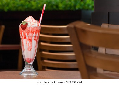 cold milk strawberry cocktail in a glass with a straw on a table