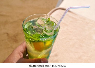Cold mojito drink on the beach sand and sunbed. Summer vacation concept image.