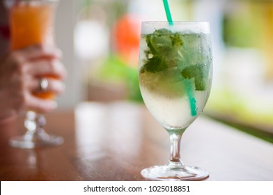 Cold Mojito with lime mint and ice on a table. Pina Colada in background