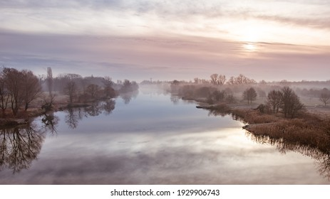 A cold morning on the Odra River in Wroclaw, a delicate fog rises above the water. River bed with calm water and trees by the shore, view from Kladka Zwierzyniecka.