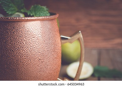 Cold Moscow Mule cocktail in copper mug on the rustic background. Shallow depth of field. Toned image.