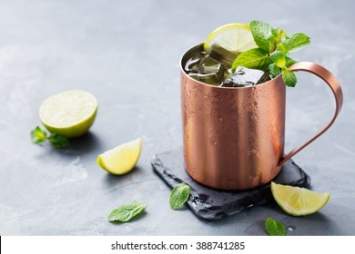 Cold Moscow Mules cocktail with ginger beer, vodka, lime. Grey stone background. Close up.