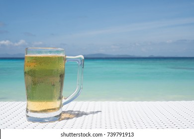 Cold mug of beer on the white rattan table at the beach restaurant with beautiful blue sea and sky background