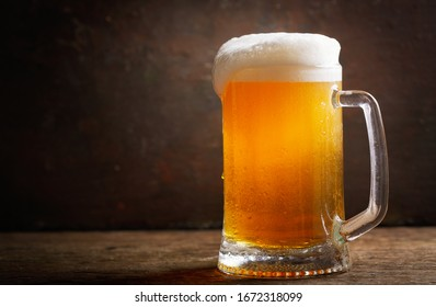 cold mug of beer on a wooden table