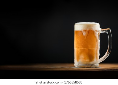 cold mug with beer, with overflowing foam, on wooden table and dark background wish space