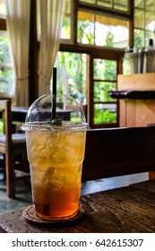 Cold peach tea in plastic cup on wooden table in coffee shop.