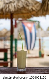 Cold pina colada cocktail in a glass on the beach with seascape background and Cuban flag. Cuba.