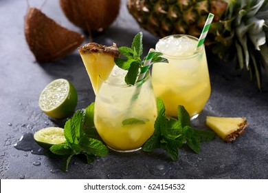 Cold pineapple cocktail with crushed ice, lime, coconut and mint, tropical refreshing lemonade drink