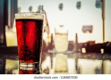 A cold pint of Irish Ale sits on the top of a table.