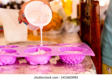 Cold pour pink soap mix being poured into pink molds for home made soap. This hobby and home business creates exotic aromatherapy organic safe soaps for luxury indulgence use