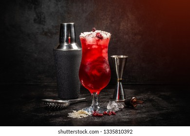 Cold red cocktail and shaker on dark background
