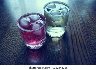 Cold red and gold soda beverages standing on a wooden surface in a cold room. Both beverages contain ice and lots of sugar. There are also water drops and bubbles.