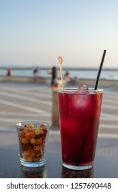 Cold red wine sangria with ice in tall glass. Cocktail snack mix in small cup. Blurred oceanfront background with a few tourists