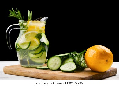 Cold and refreshing detox water with lemon, cucumber, rosemary and ice in glass jar. Copyspace. Banner