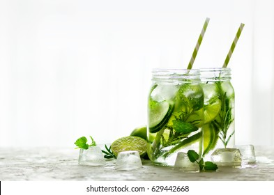 Cold and refreshing detox water with lime, cucumber, rosemary and ice in glass jar. Copyspace