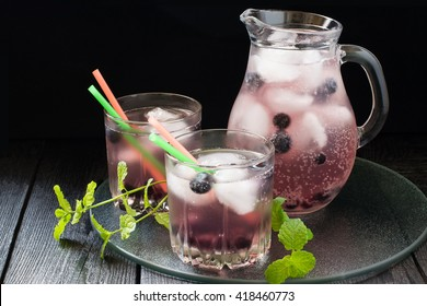Cold refreshing drink with blueberries, black currants, juice, soda water and ice in a jug and a glass of cocktail straws on a dark background