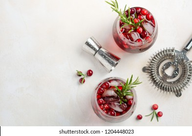 Cold refreshing drink with cranberries and rosemary on a white concrete background