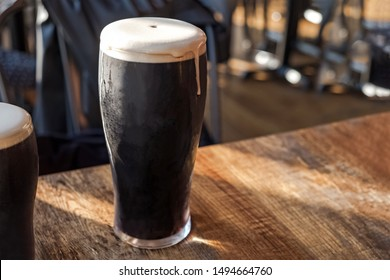 Cold refreshing glass of stout beer cloe-up standing on the wooden table in the pub