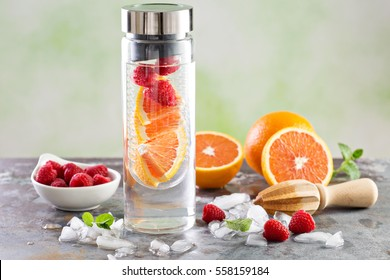Cold and refreshing infused detox water with raspberry and orange in glass bottle