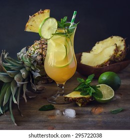 Cold refreshing pine apple cocktail drink with lime and mint for hot summer day, mojito idea, homemade lemonade with cubes of ice
