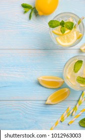 Cold refreshing summer drink with lemon and mint on light blue wooden background, top view, flat lay, copy space.