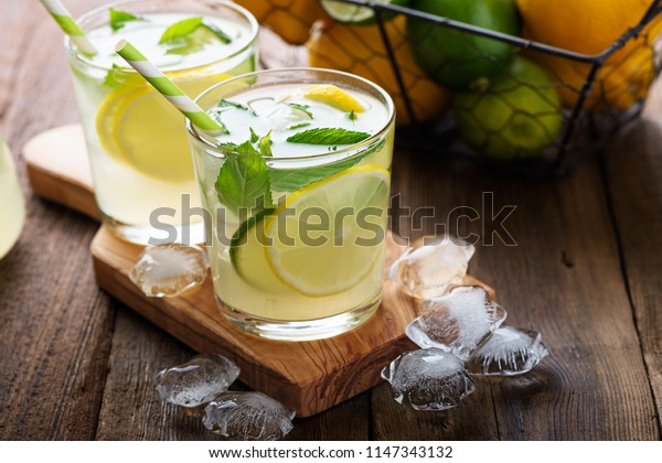 Cold refreshing summer lemonade  in a glass on wooden background.
