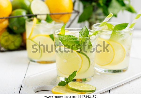 Cold refreshing summer lemonade  in a glass on white wooden background.