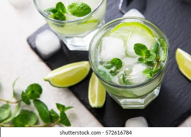 Cold refreshing summer lemonade mojito in a glass on a slate board and stone background