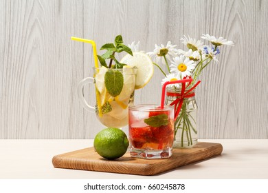 Cold refreshing summer lemonade mojito with lemon slices and mint in a tall glass and strawberry lemonade with mint in a short oneon an wooden cutting board
