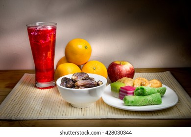 Cold refreshing syrup drinks, sweet dates, kuih are simple and common iftar break fast food during fasting month of Ramadan. Fine art rendition.