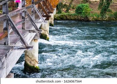 Cold river flowing under the rustic wooden bridge, Krka, Croatia